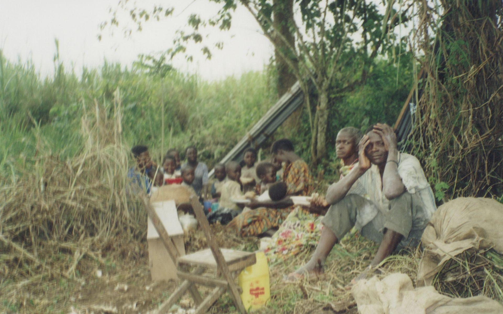 Foto einre Filmszene: afrikanische Menschen auf dem Boden sitzend vor einem Baum, Busch im Hintergrund