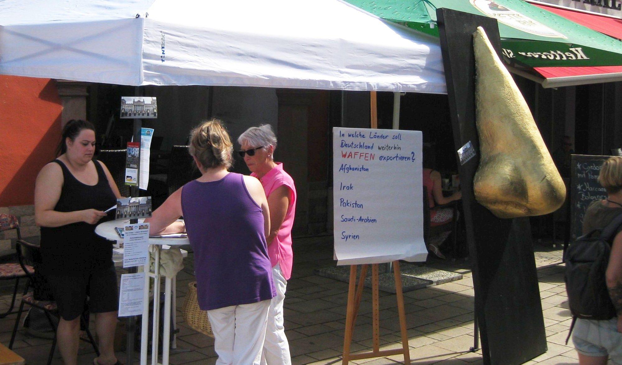Foto eines Standes mit Pavillon und 4 Personen, sowie einer übergroßen vergoldeten Nase und einem Fragebogen