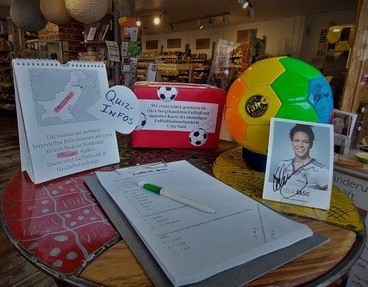 Fußballquiz, Quizinfos, eine Box für die Teilnahmezettel, Ball in Regenbogenfarben plus Autogrammkarte von der ehemaligen Fußball-Nationalspielerin Célia Šašić