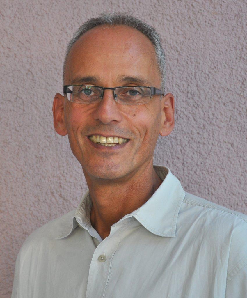 Portraitfoto: Mann mit rahmenloser Brille und kurzen, grauen Haaren mit hellem Hemd.