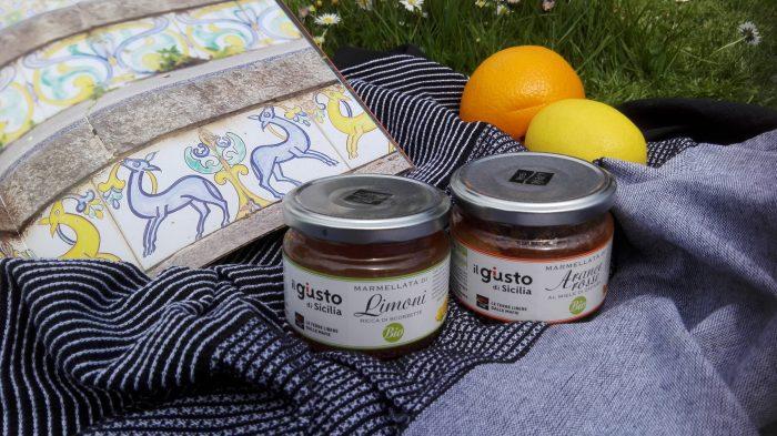 Gläser Zitronen- und Orangenmarmelade von Libera Terra auf Decke mit Orange, Zitrone und Buch mit Abbildung von italienischen Fliesen