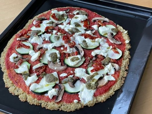 Foto: Pizza mit Quinoa-Boden belegt mit Champigons, Zucchine, getrocknete Tomaten, pürierte Tomaten, Feta/Schafskäse, Basilikumpesto