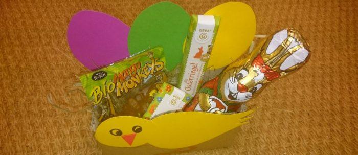 Foto: aus buntem Papier gebasteltes Körbchen, Vorderseite gelber Vogel, Rückseite 3 verschiedenfarbige Eier. Im Körbchen Süßigkeiten aus dem Fairen Handel