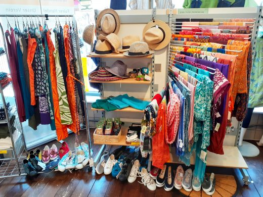 Foto: Sommerkleider auf einem Ständer, Hüte, Schals, Socken in einem Regal, Tücher an einem Fächerständer