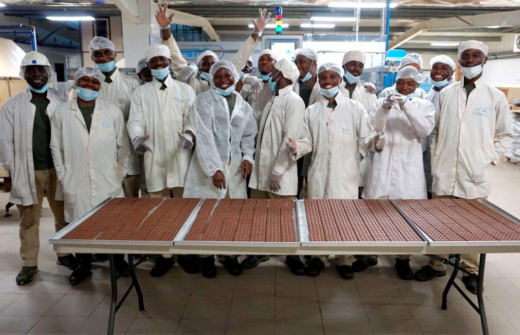 Lachende Ghanaer in weissen Kitteln, mit weißen Hauben und Mundschutz, stehen in einer Fabrik, davor ein Tisch voll mit unverpackten Schokoladetafeln, fein säuberlich neben- und hintereinanderliegend