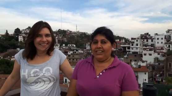 Foto: 2 Frauen auf einem Balkon vor Stadtpanorama, Tasco, Mexico